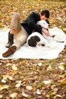 Homem e cão relaxando no cobertor do piquenique — Fotografia de Stock