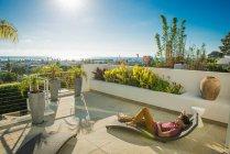 Молода людина, лежачи на шезлонгу в саду Пентхаус на даху, La Jolla, Каліфорнія, США — стокове фото