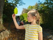 Young girl looking at leaf in the garden — Stock Photo