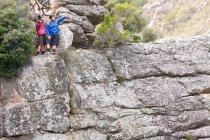 Mountain bike coppia guardando fuori dalla formazione rocciosa — Foto stock