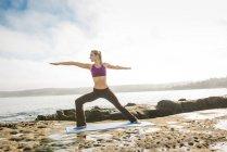 Woman doing yoga at coast — Stock Photo