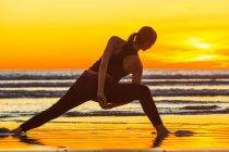 Практикуючі йогу жінка на пляжі — стокове фото