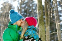 Couple wearing knit hats, kissing — Stock Photo
