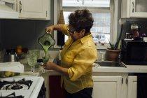 Woman pouring smoothie in kitchen — Stock Photo