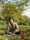 Donna sotto l'albero che ascolta musica — Foto stock