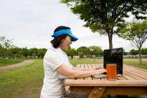 Femme à l'aide de portable sur banc de pique-nique dans le parc — Photo de stock