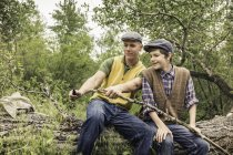 Man and boy wearing flat caps sitting on fallen tree whittling twig with penknife — Stock Photo
