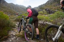 Молодая женщина толкает горный велосипед вверх по горной тропе — стоковое фото