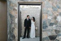 Жених и невеста, на улице, держатся за руки, улыбаются — стоковое фото