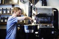 Junger Mann gibt Kaffeebohnen an Kaffeeröster im Café — Stockfoto