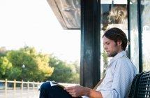Hombre espera en la estación de tren y leyendo periódico - foto de stock