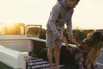 Coppia che si tiene per mano sul retro del pick-up a Newport Beach, California, USA — Foto stock