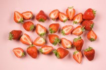 Whole and halved strawberries on pink background — Stock Photo