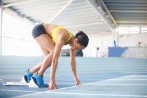Jeune athlète féminine sur les starting-blocks — Photo de stock