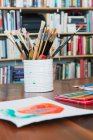 Children paintbrushes and paintings on table — Stock Photo