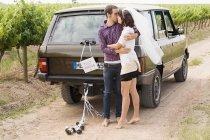 Couple nouvellement marié embrasser par véhicule — Photo de stock