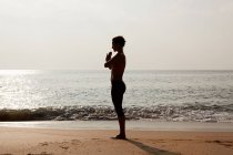 Silhouette of woman by sea in prayer pose — Stock Photo
