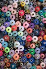 Pile of multi colored cotton reels — Stock Photo