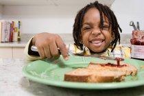 Portrait of Boy spreading jam on toast — Stock Photo