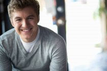 Portrait of young smiling man in cafe — Stock Photo