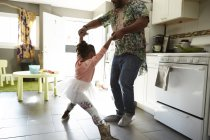 Father and daughter playing in kitchen — Stock Photo