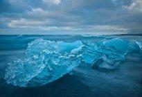 Gletscher am Strand unter wolkenverhangenem Himmel — Stockfoto