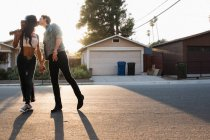Young couple kissing outdoors, young woman holding guitar — Stock Photo