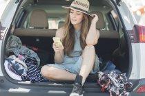 Mujer contemporánea en la parte posterior de hatchback mirando el teléfono inteligente - foto de stock