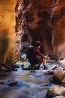 Senderista masculino sentado en una cueva en River Rock, Parque Nacional Zion, Utah, EE.UU. - foto de stock