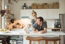Paar mit Katze am Küchentisch — Stockfoto