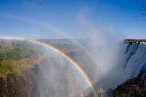 Rainbows in bright sunlight above Victoria Falls — Stock Photo