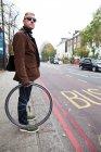 Cyclist holding bike wheel — Stock Photo
