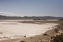Salt flats with distant view of campers and off road vehicles, Ibex, Utah, USA — Stock Photo