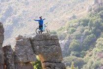 Junger Mann mit Mountainbike und Arme ausgestreckt auf Felsen — Stockfoto
