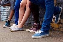 Jambes d'adolescents debout dans une rangée — Photo de stock