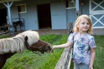 Kleines Mädchen füttert ein Pony im Freien — Stockfoto