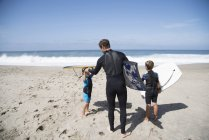 Vista posteriore del padre e due figli che si preparano ad andare a fare bodyboard sulla spiaggia, Laguna Beach, California, USA — Foto stock