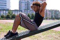 Junger Mann macht Sit-ups im Outdoor-Fitnessstudio — Stockfoto