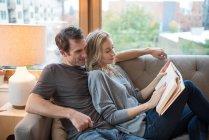 Casal reclinado no sofá e livro de leitura — Fotografia de Stock