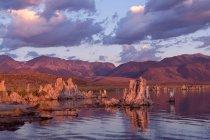Мальовничим видом хмарного неба захід сонця над озеро з скельними утвореннями — стокове фото