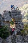 Mountain biking couple on rock formation — Stock Photo