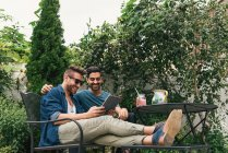 Young male couple sitting in garden and looking at digital tablet — Stock Photo
