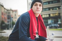 Young male runner taking a break in city — Stock Photo