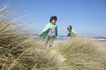 Two young boys, wearing fancy dress, playing on beach — Stock Photo
