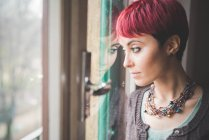 Young woman looking out of window, pensive expression — Stock Photo