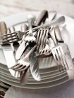 Cutlery piled on stack of plates — Stock Photo