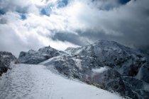 Vista in lontananza di un escursionista sulla cima di montagna innevato — Foto stock