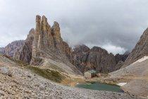 Bâtiment industriel et le lac dans la vallée, Dolomites, Italie — Photo de stock