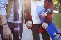 Sezione centrale della giovane donna skateboarder che si tiene per mano con il fidanzato nel parco — Foto stock