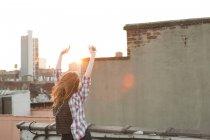 Молодая женщина, слушать музыку с поднятыми на крыше города — стоковое фото